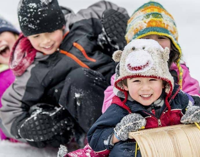 Kids sledding in the winter in Snowmass, Colorado